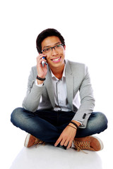 Happy asian man sitting on the floor and talking on the phone