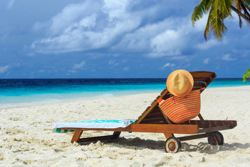 straw hat and bag on a lounge chair at tropical beach