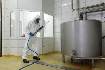 worker in  uniform, with high pressure washer at  plant