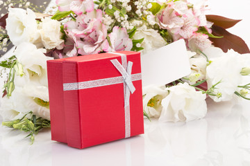 gift and flowers on white