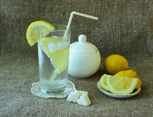 Cold glass of lemonade, sugar and lemon.