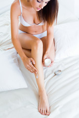 Beautiful pretty young woman caring about her legs with moisturi