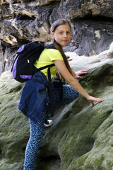girl climbs on a rock outdoors