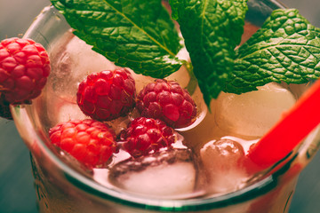 Red drink with raspberries, ginger and ice
