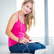 Pretty, young female student listening to music on her tablet