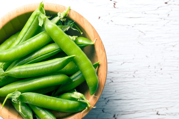 green pea pods in wooden bowl