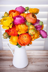 Persian buttercup flowers in a vase with sun light coming out of