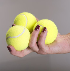Three tennis balls in a players hand