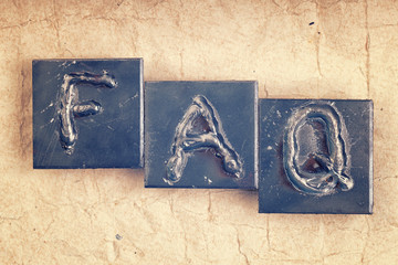 "The abbreviation ""FAQ"" made from metal letters on an old vintage"