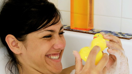 Girl playing with two ducks in bath tub