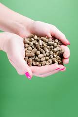 female hands holding the green background of pellets