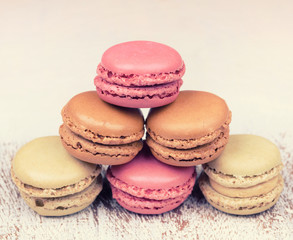Colorful fresh delicious macaroons on vintage wooden background