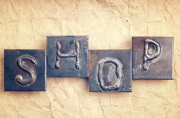 """The word """"SHOP"""" made from metal letters on an old vintage paper"""