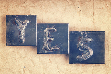 """The word """"YES"""" made from metal letters on an old vintage paper b"""