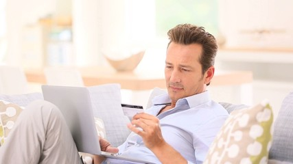 Handsome man relaxing in sofa and shopping on internet