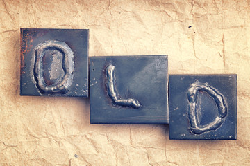 "The word ""OLD"" made from metal letters on an old vintage paper b"