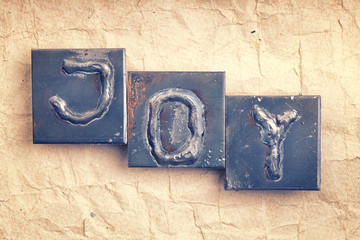"""The word """"JOY"""" made from metal letters on an old vintage paper b"""