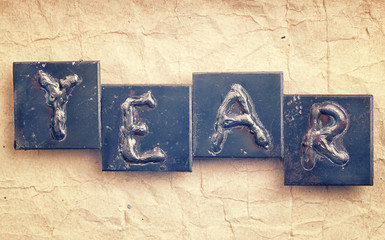 """The word """"YEAR"""" made from metal letters on an old vintage paper"""