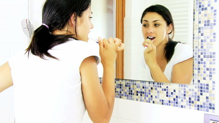 Medium shot of happy young woman brushing teeth