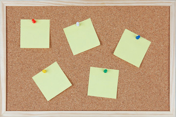 Six post-it notes with pins sticked on corkboard