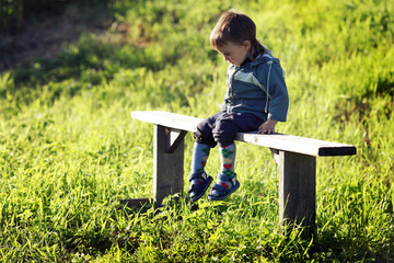 little upset boy sitting on a bench in a field