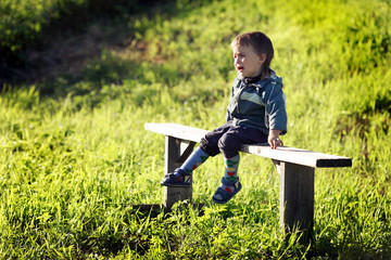 sobbing little boy sitting on a bench in a field