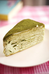 close up green tea crepe cake in white dish