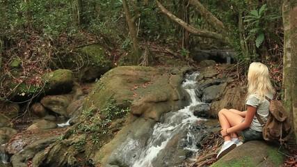 Girl walking near the creek in the jungle