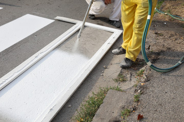 Roadworks, street lines painting, worker and spray gun