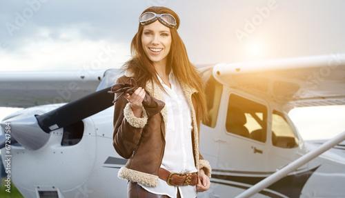 Leinwandbild Motiv Portrait of young beautiful woman pilot in front of airplane.