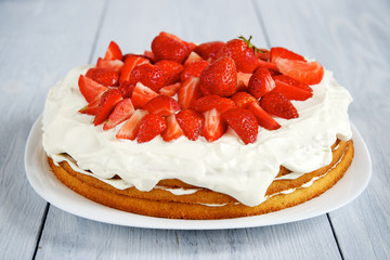 Strawberry cake with whipped cream on white wooden table