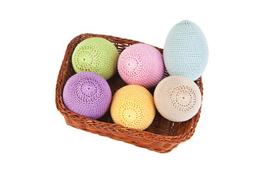 Colorful crocheted eggs in a wicker basket