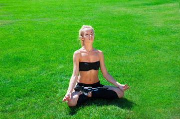 a young sport girl meditates on the grass