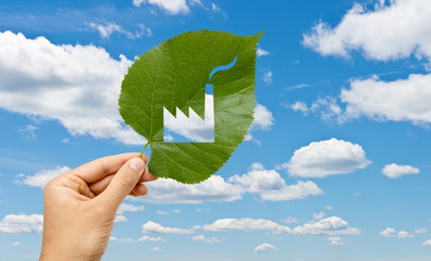 Hand holding leaf with a factory cutted against sky