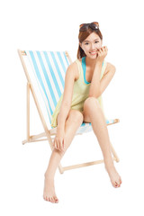 pretty sunshine girl smiling and sitting on a beach chair