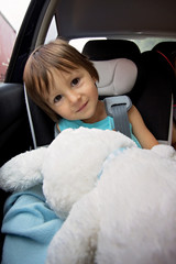 Adorable baby boy in safety car seat, holding teddy rabbit