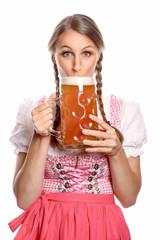 Attraktive Frau im Dirndl trinkt aus einem Maßkrug