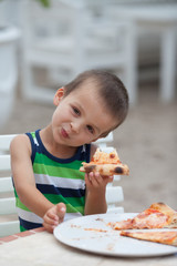 Adorable boy, eating pizza
