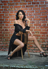 Charming young brunette woman in black near red brick wall