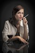 Portrait of woman with glass of wine and cigarette