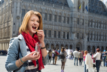 Woman eating chocolate on Grand Place in Brussels