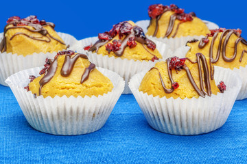 Cupcakes with cranberries on a blue tablecloth