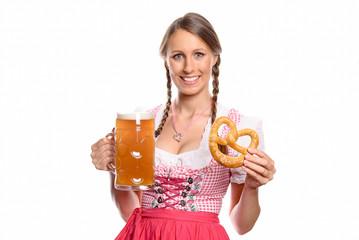 Lächelnde Frau im Dirndl mit einem Bier und Brezel
