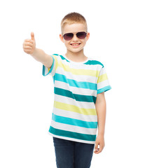 smiling little boy in sunglasses showing thumbs up