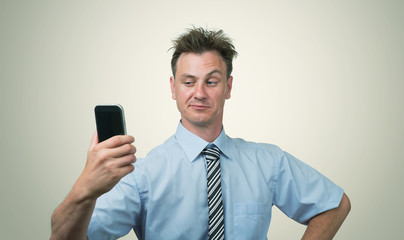 Businessman photographing himself on a smartphone