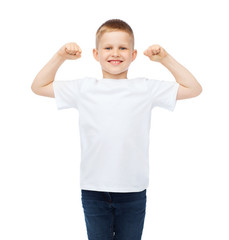 little boy in blank white t-shirt showing muscles