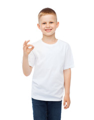little boy in white t-shirt showing ok gesture