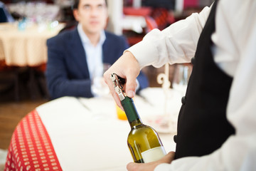 Waiter uncorking a wine bottle