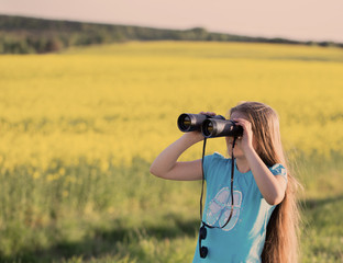 girl looking through binoculars outdoor