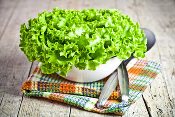 lettuce salad in a bowl and spoons